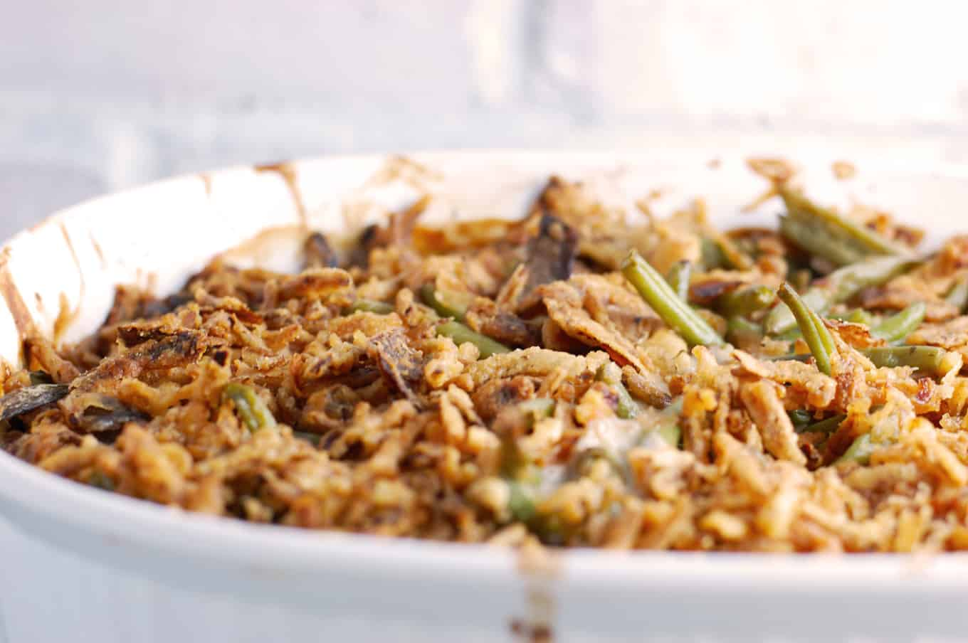 Vegan green bean casserole. Green beans tossed with sauteed mushrooms, onions, and vegan mushroom gravy. Topped with french fried onions and baked in the oven until crispy. Perfect sidedish for a vegan Thanksgiving.