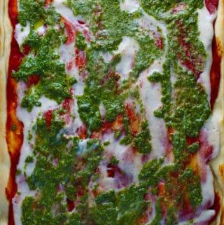 vegan mozzarella on top of pizza with tomato sauce and basil pesto