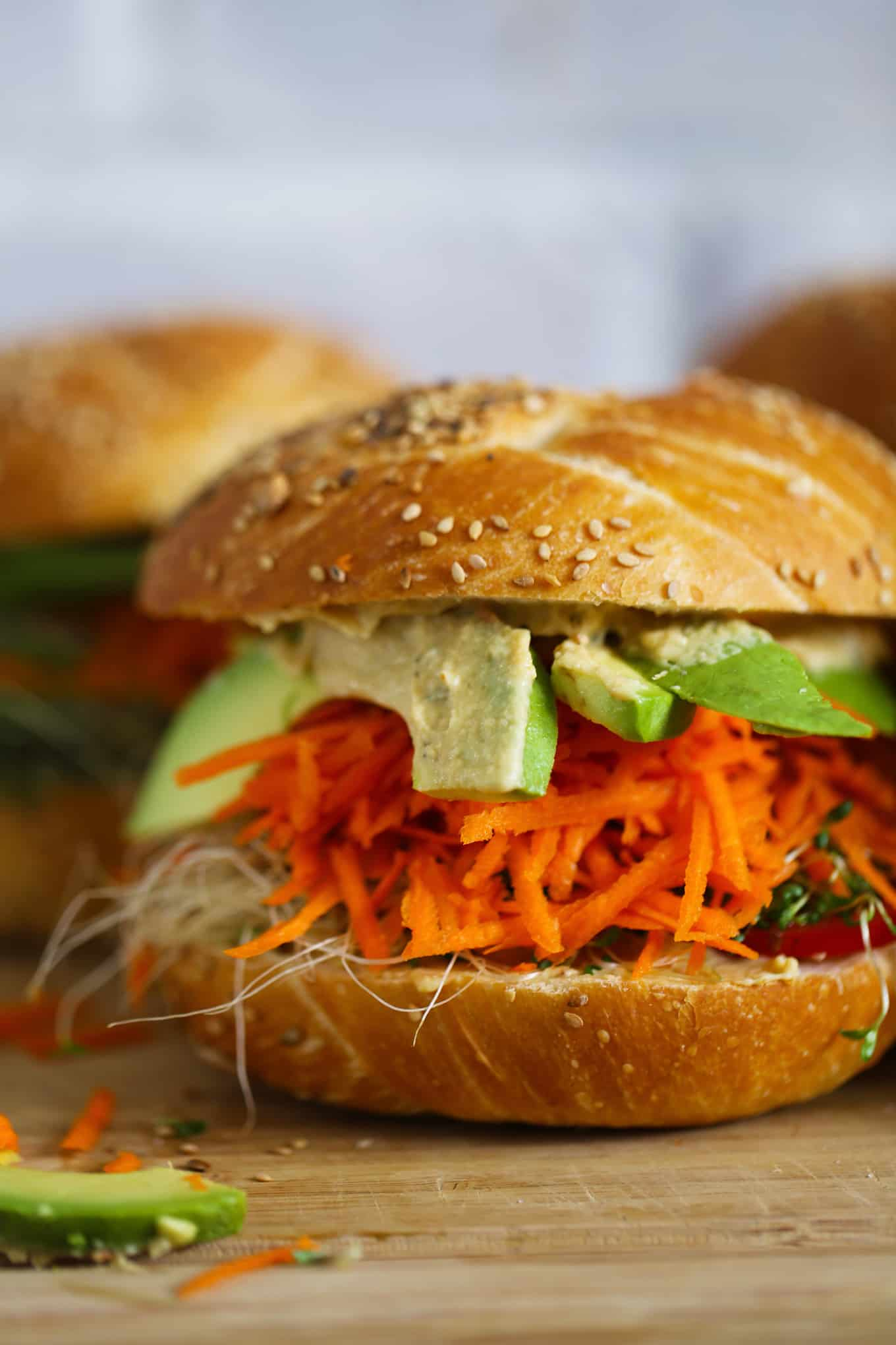 Hummus and avocado sandwich- A roll topped with hummus, tomato, grated carrot, avocado, and sprouts