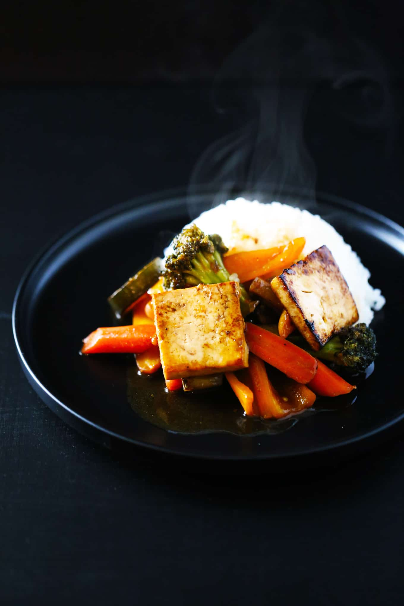 str-fry veggies & tofu with stir-fry sauce and rice on a black plate.