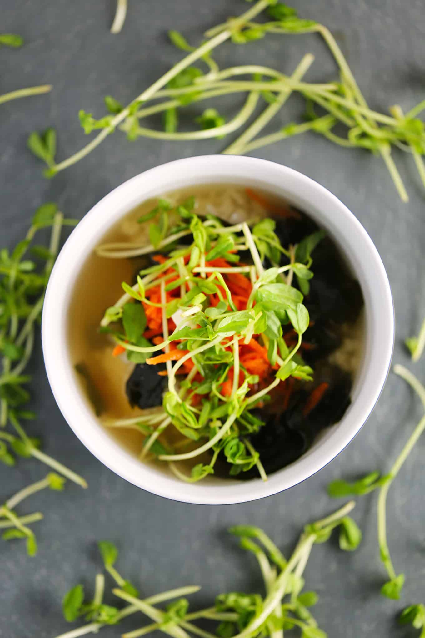 vegan miso soup in a bowl with sushi rice, pea shoots, and grated carrots